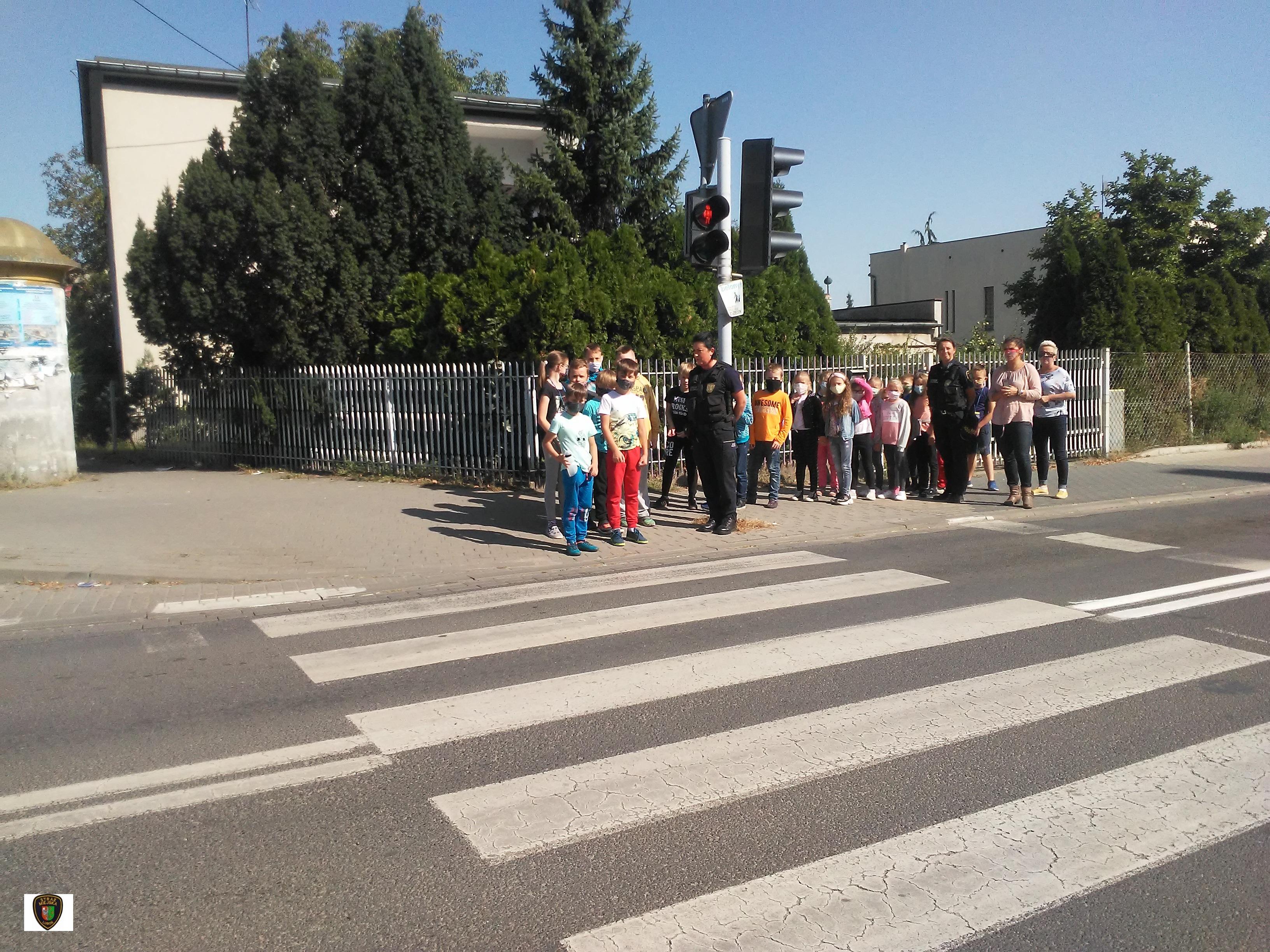 zdjęcie przedstawia dzieci stojące przed przejściem dla pieszych w obecności strażników miejskich