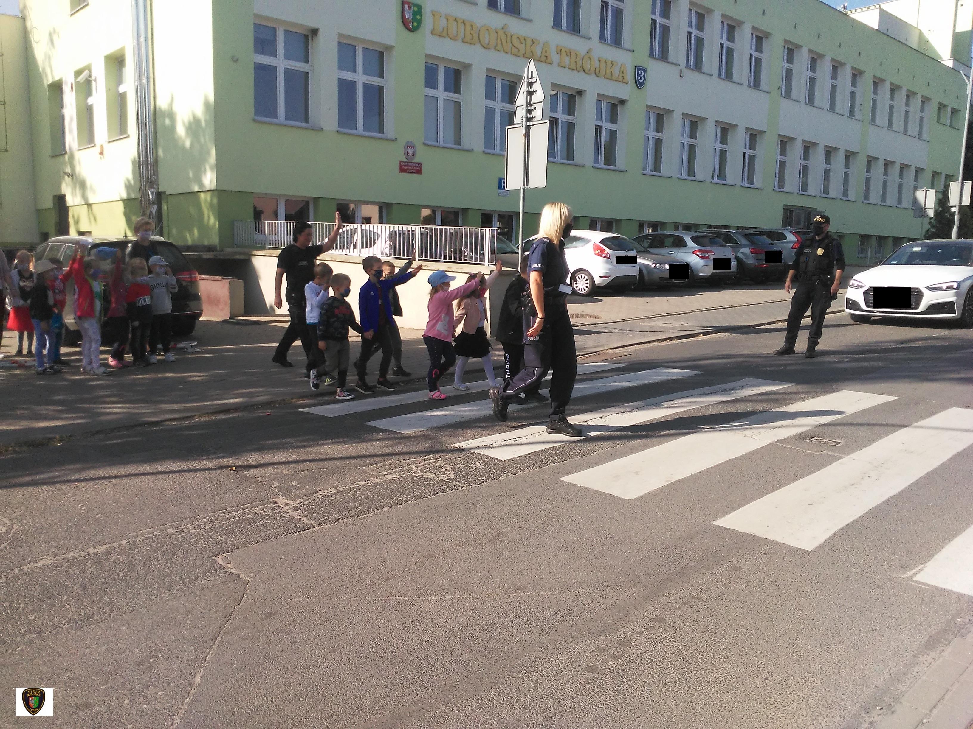 zdjęcie przedstawia dzieci przechodzące przez przejście dla pieszych w obecności funkcjonariuszy straży miejskiej i policji