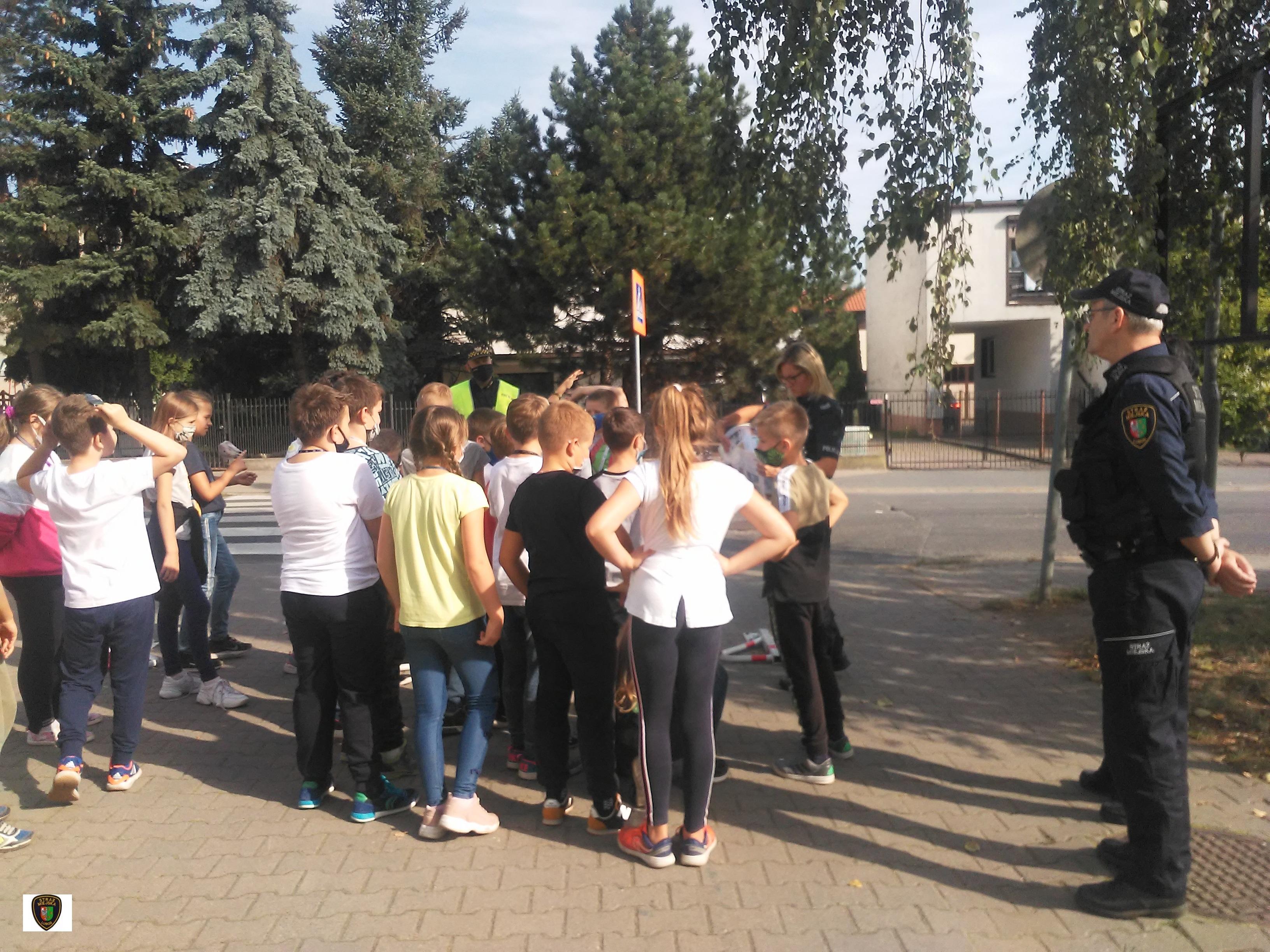 zdjęcie przedstawia dzieci stojące podczas prelekcji prowadzonej przez funkcjonariuszkę policji