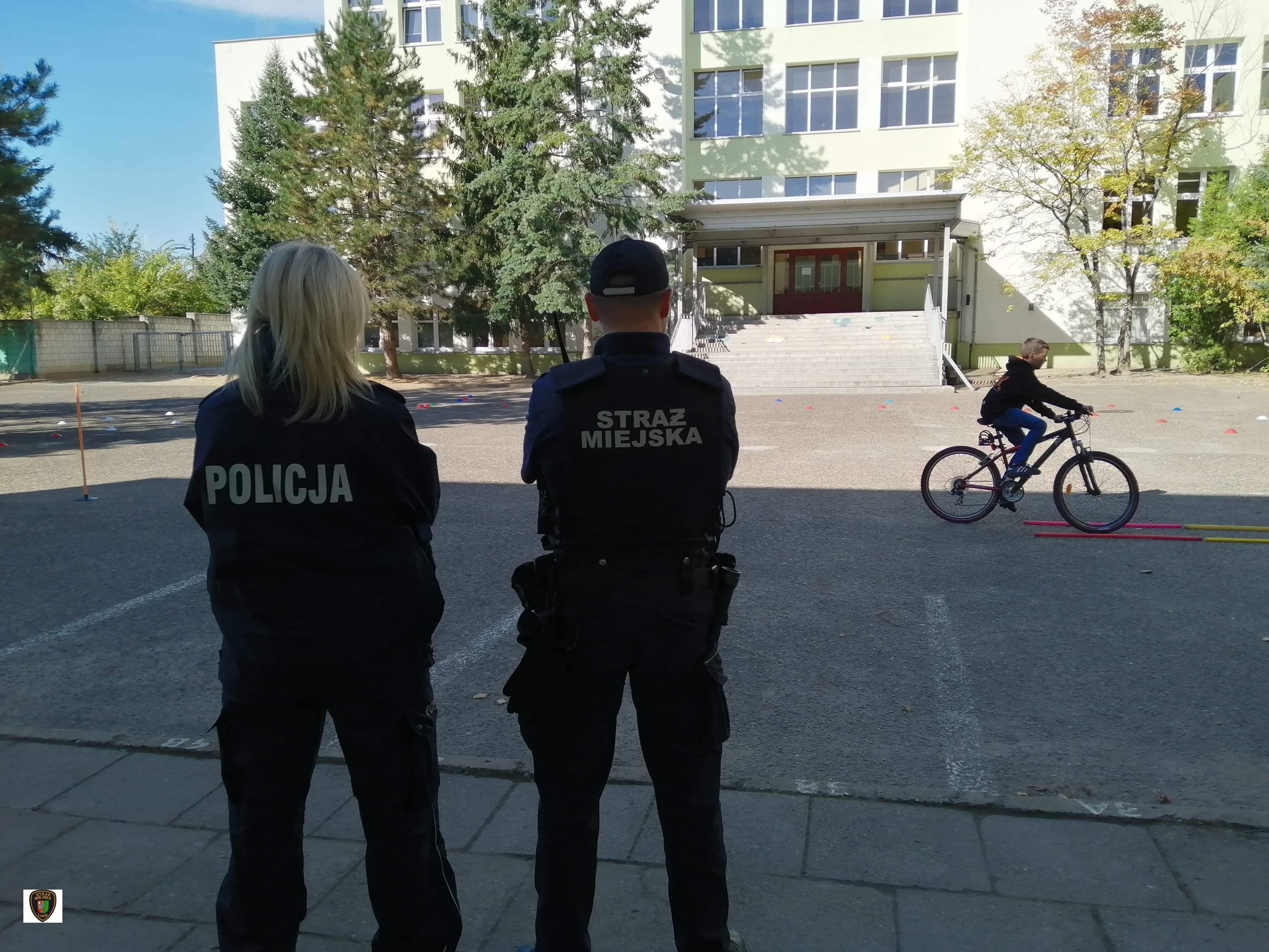 Zdjęcie przedstawia stojących policjantkę i strażnika miejskiego oraz dziecko jadące rowerem podczas egzaminu na kartę rowerową