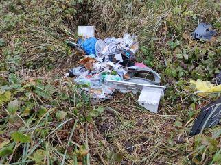 Zdjęcie przedstawia śmieci leżące na trawie