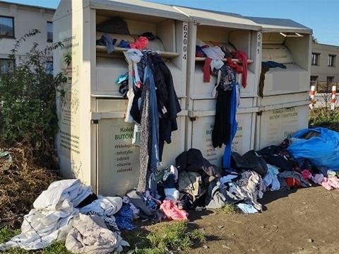 Zdjęcie przedstawia przepełnione pojemniki na odzież używaną