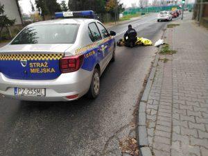 Zdjęcie przedstawia strażnika miejskiego udzielającego pomocy osobie leżącej