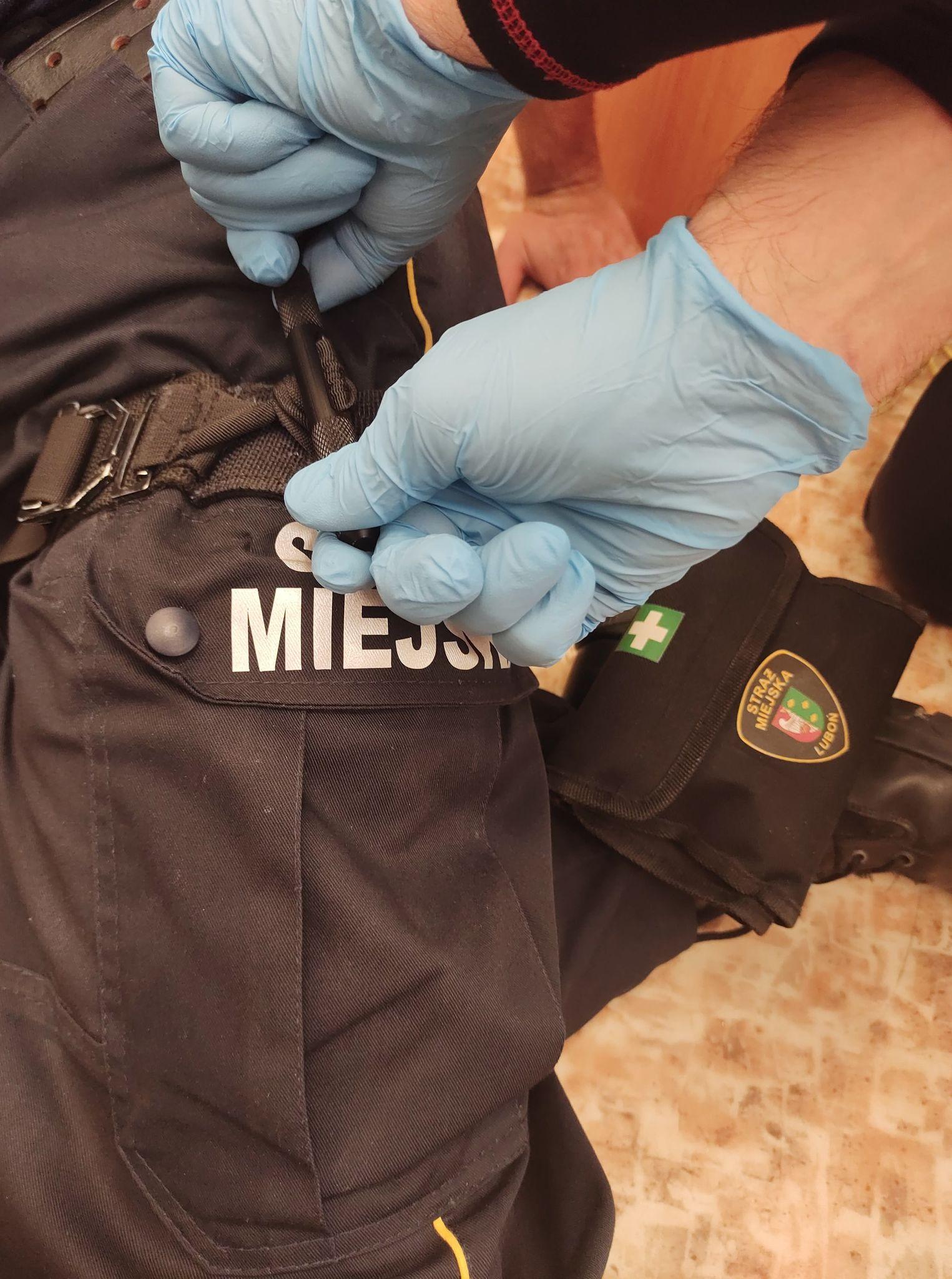 Zdjęcie przedstawia strażnika używającego opaskę uciskową - stazę