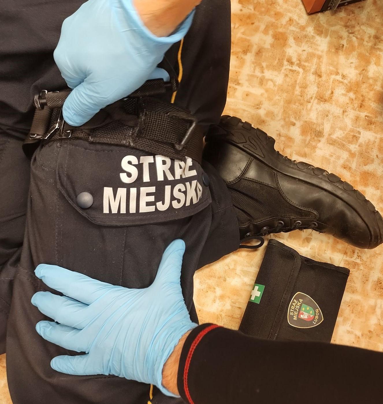 Zdjęcie przedstawia strażników miejskich podczas używania opaski uciskowej - stazy taktycznej