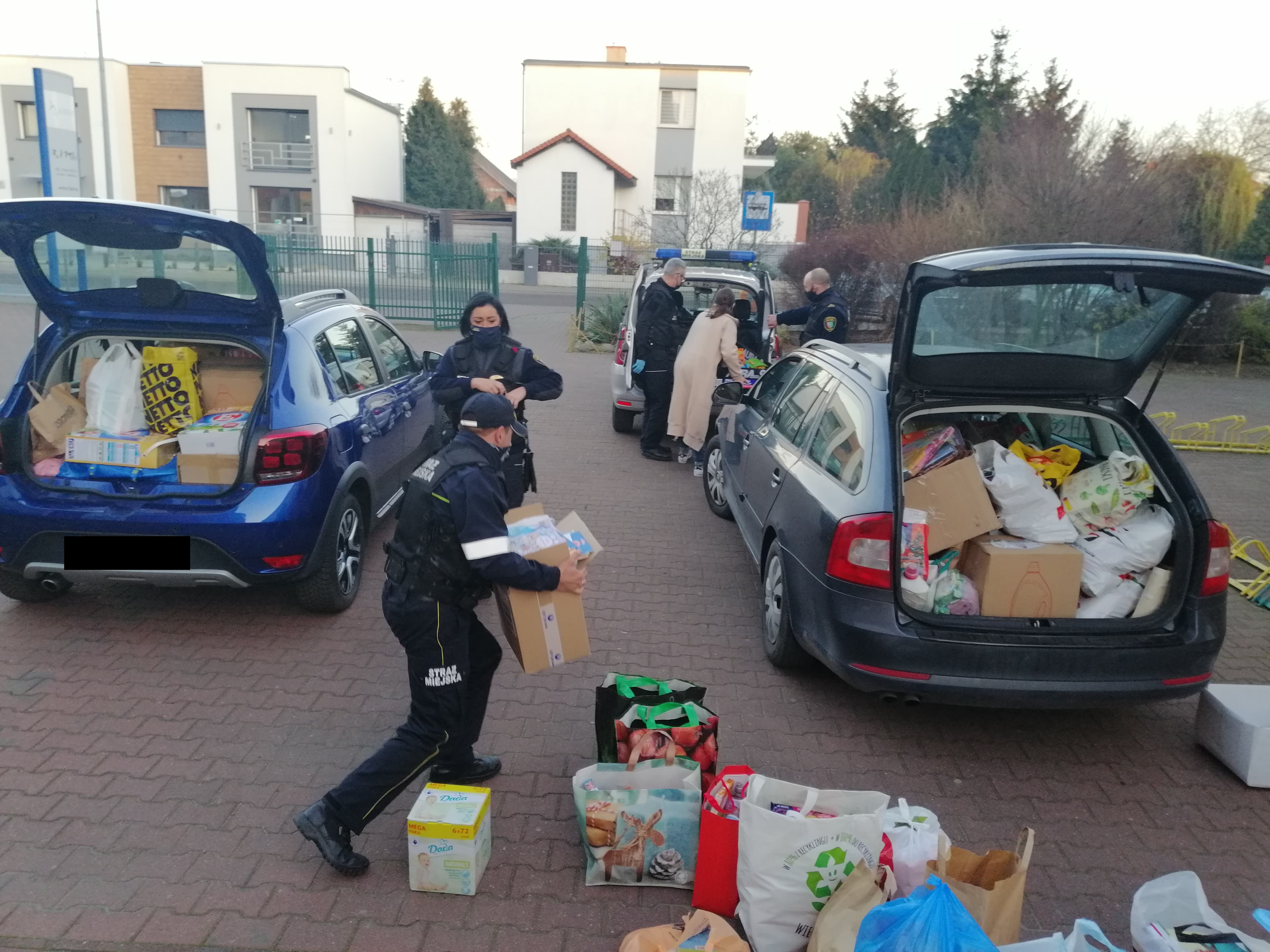 djęcie przedstawia strażników miejskih pakujących przedmioty do samochodów przed odwiezieniem do Hospicjum Domowego