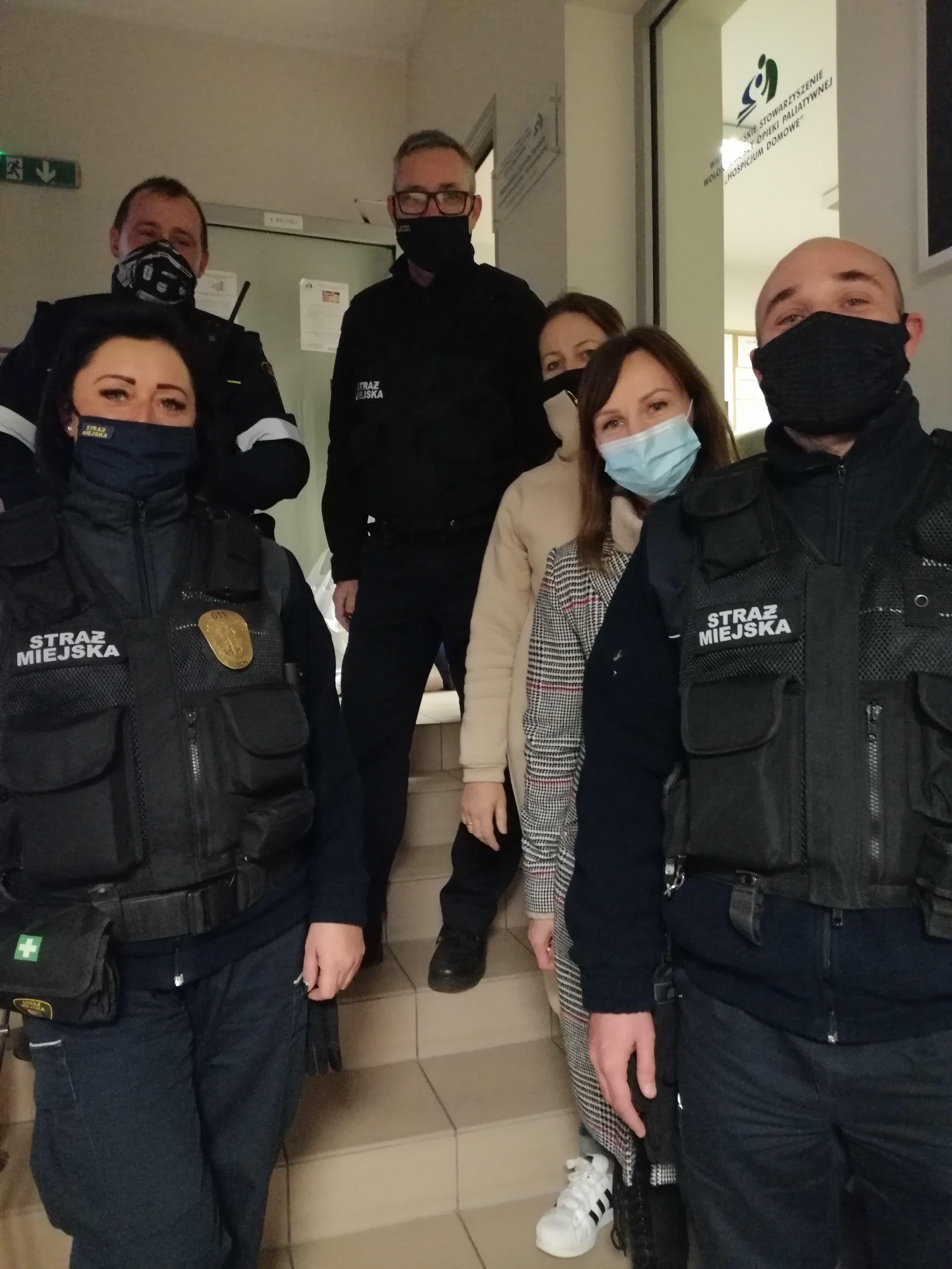 Zdjęcie przedstawia strażników miejskich i nauczycieli SP5 przed przewiezieniem zebranych przedmiotów do Hospicjum Domowego