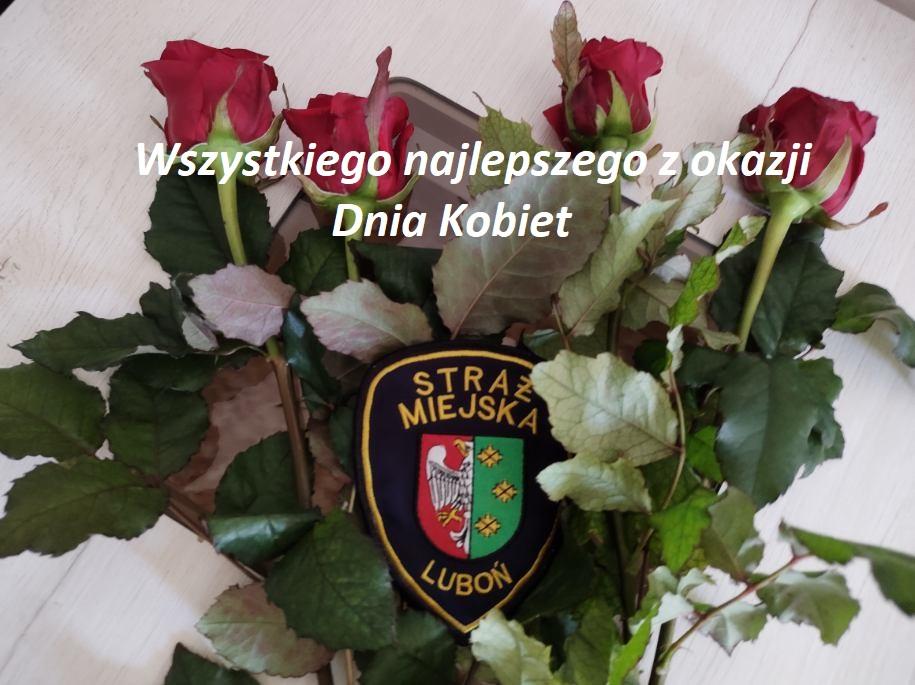 Zdjęcie przedstawia czerwone róże oraz znak identyfikacyjny Straży Miejskiej Miasta Luboń