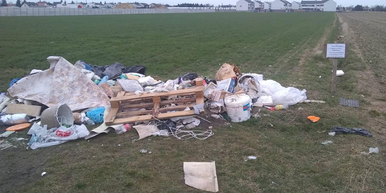 Zdjęcie przedstawia śmieci wyrzucone na pole