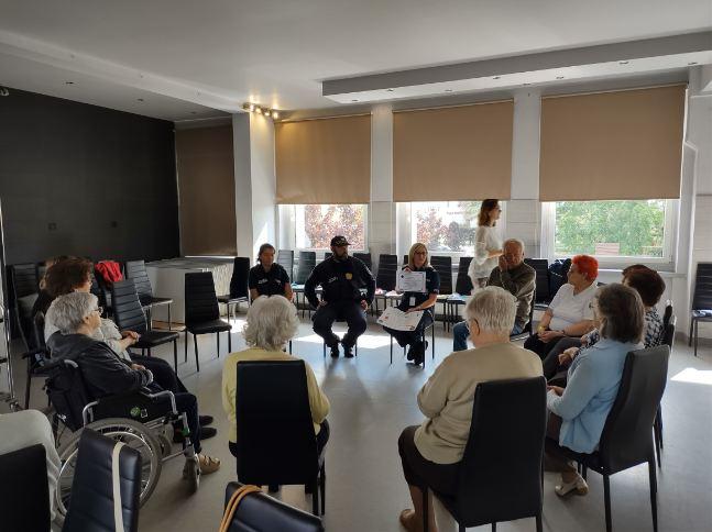 Zdjęcie przedstawia osoby obecne na prelekcji w temacie zagrożeń bezpieczeństwa osób starszych dla seniorów w Senior-Wigor w Luboniu