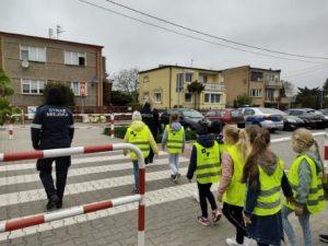 Zdjęcie przedstawia dzieci przechodzące przez przejście dla pieszych z policjantem i strażnikiem miejskim