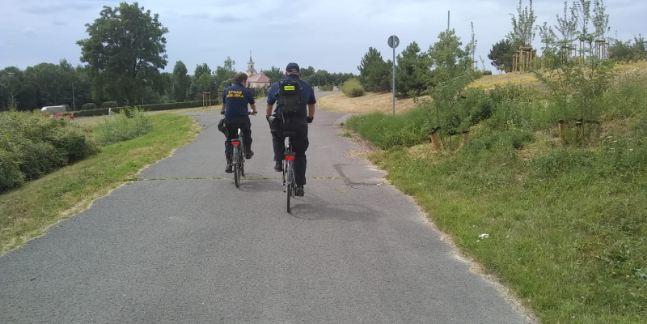Zdjęcie przedstawia strażników miejskich jadących rowerami